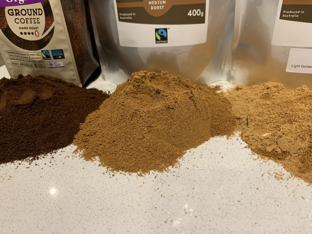 3 coffee grinds lay next to each other left is a supermarket dark roast middle and right are James Health 1000 Plus Medium and Light Golden Roast Coffee enema grinds