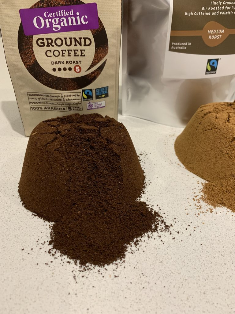 ground coffee from a supermarket organic and fairtrade piled on a benchtop showing the dark colour